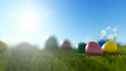 Colorful Easter eggs on green meadow over bright sun Animation