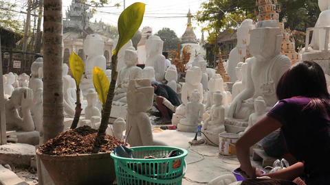 Young Woman finishing marble Buddha statue in Mandalay with pagodas view Footage
