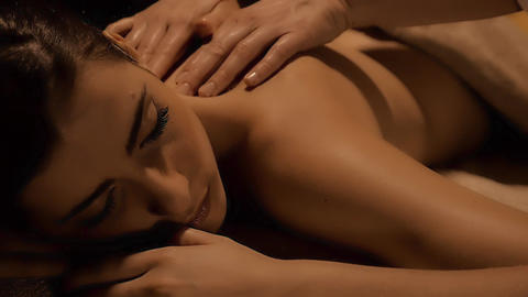 Woman getting massage relaxing in spa in luxury hotel dolly shot closeup Footage