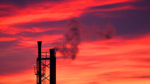 An industrial pipe with smoke against a background of crimson sky Footage