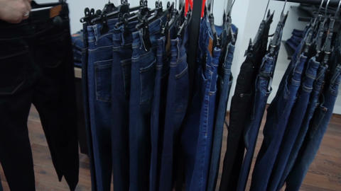 Shop assistant hangs jeans on stand in boutique Filmmaterial