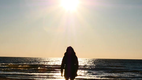 warmly clothed womans recessive silhouette motion to sea and sun side Footage