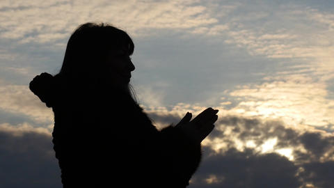 silhouette of praying woman with beautiful sky background Footage