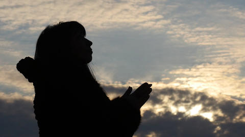 silhouette of woman making Christian pray with beautiful sky background slow mot Footage