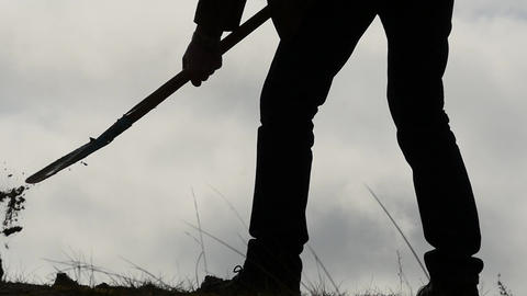 silhouette of man digging a hole with a shovel slow motion close up Footage