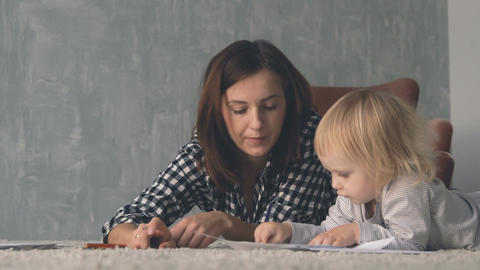 Mother with little baby are drawing with colorful pencils Footage