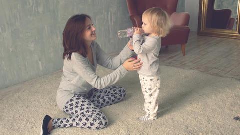 Little cute girl drinks water from bottle Footage