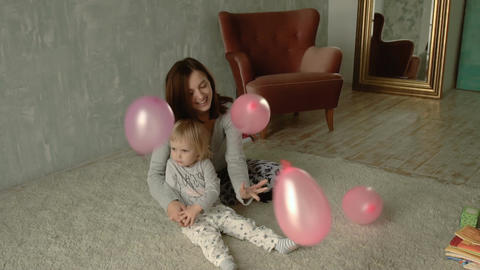 Mother and her little daughter plays with balloons Footage