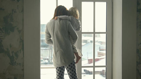 Mother with little daughter looking out the window Footage