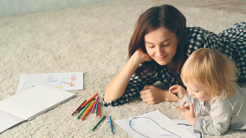 Baby girl draws a picture with pencils. Mother hugs and kisses her Footage