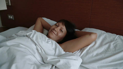 Sleepy woman lying in bed waking up and smiling Footage