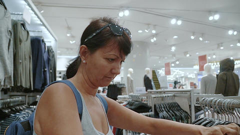 Woman looking at clothes in clothes store Footage