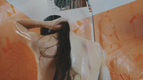 Brunette girl taking shower. Relax. Body care. Hygiene. Wash hair. Soap foam Footage