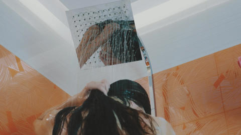 Brunette girl taking shower. Relax. Body care. Hygiene. Wash hair. Water Footage