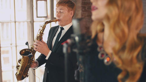 Jazz vocalist perform on stage with saxophonist in dinner jacket. Click fingers ビデオ