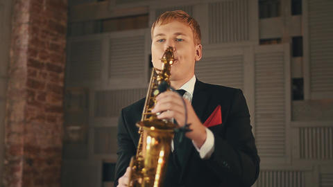 Saxophonist in dinner jacket stand on stage with golden saxophone. Jazz musician Footage