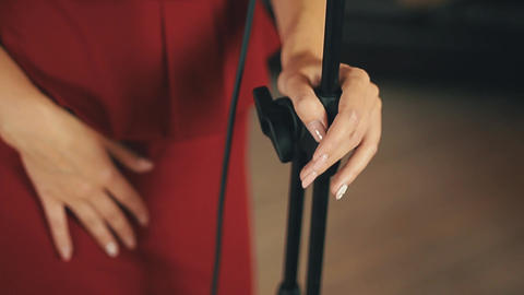 Elegant vocalist in red dress holding a microphone. Retro style. Dancing Footage
