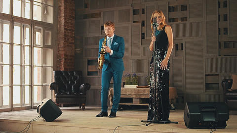 Jazz vocalist in glare dress and saxophonist in blue suit on stage. Performance Footage
