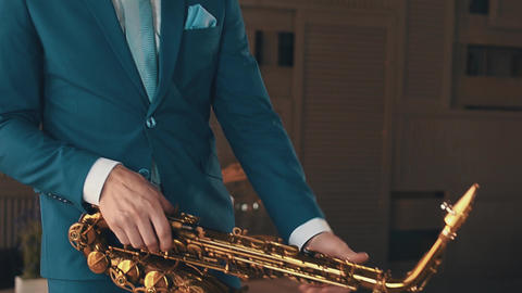 Saxophonist in blue suit start play jazz on golden saxophone at stage. Elegance Footage