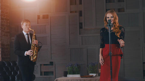 Jazz duet on stage. Saxophonist. Vocalist in retro style dress click fingers ビデオ