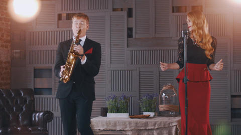 Jazz duet on stage. Saxophonist. Attractive vocalist sing and click fingers ビデオ