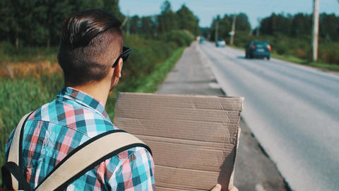 Young boy hitchhiking at road with cardboard plate in summer sunny day. Travel Footage
