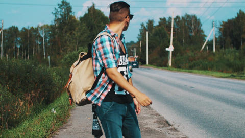 Boy in sunglasses with backpack walking along roadside. Hitchhiking. Thumb up Footage