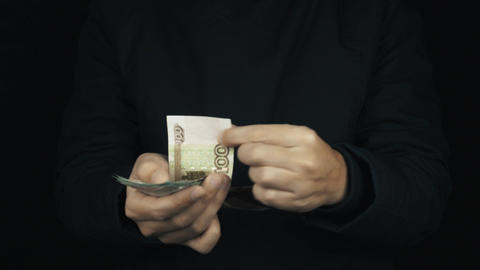 Male hand in long sleeve jacket pull hidden pile of money bills up, counting it Footage