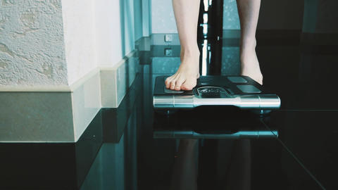 Girl walk on floor stand up on modern scales in apartment. Weighing. Slimness Live Action