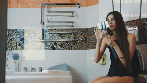 Brunette girl sit on toilet in bathroom hold smartphone in blue monopod Footage