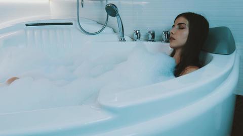 Brunette girl petting herself in bathtub full of foam. Enjoyment. Satisfaction Live Action