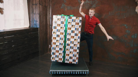 Magician in red shirt in studio use telekinesis makes big present box levitate Live Action