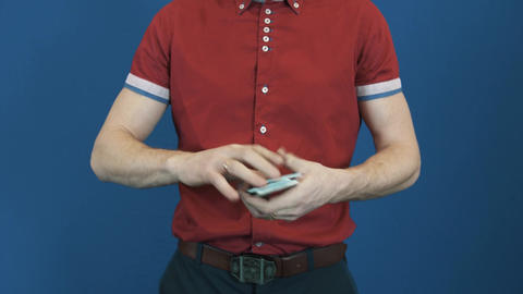 Close up man in red shirt on red back ground showing playing card shuffle trick Live Action
