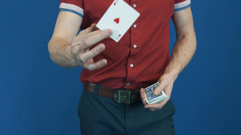 Close up magician in red shirt showing playing cards magic focuses Footage