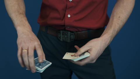 Close up conjurer in red shirt showing playing cards magic focuses Footage