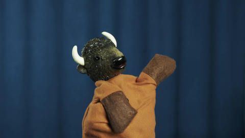 Ox hand puppet playing air guitar and shake head on scene with blue background Footage