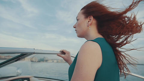 Red hair girl in dress on motor boat. Beautiful summer windy evening. Freedom Footage