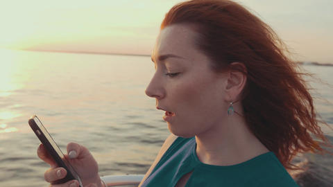 Girl in turquoise dress steer motor boat. Tap in smartphone. Beautiful sunset Footage