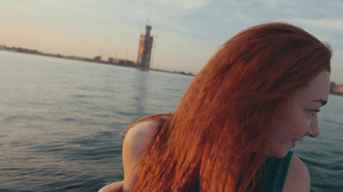 Girl in turquoise dress steer motor boat. Summer sunset.... Stock Video Footage