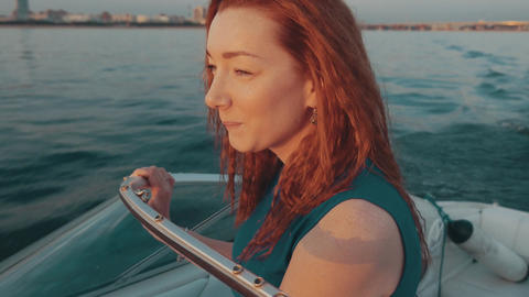 Red hair girl in turquoise dress steer motor boat. Summer sunset. Entertainment Footage