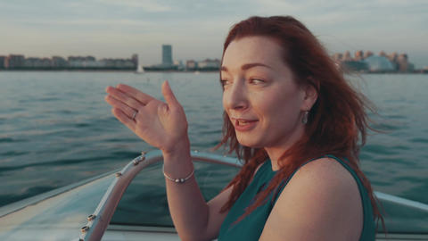 Red hair girl in turquoise dress drive motor boat talk with boy. Summer evening Footage