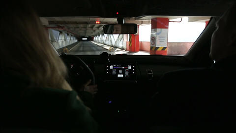Woman driving car inside covered parking structure Footage