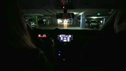 Girl driving car in covered parking garage Footage