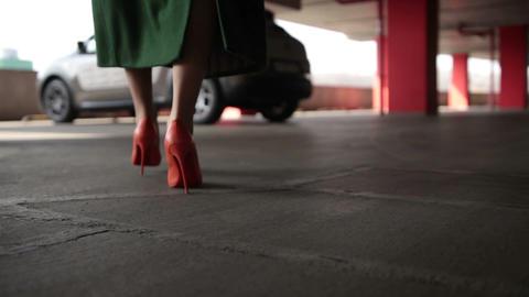 Elegant female legs walking to parked car Footage