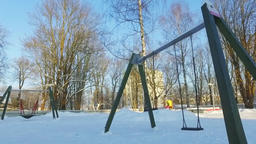 Walk along the city covered with snow. Kids playground. Sunny winter day Footage