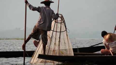 Fishers on boat in waters at Inle lake of Myanmar - view from rocking boat Footage
