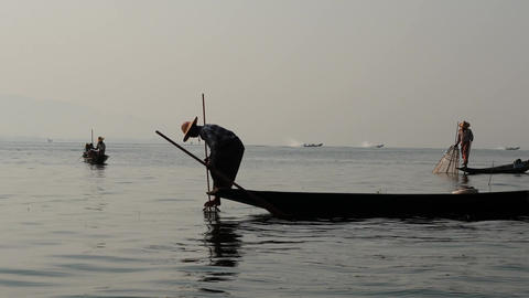 Fishers silhouette on boat in waters at Inle lake of Myanmar - view from rocking Footage