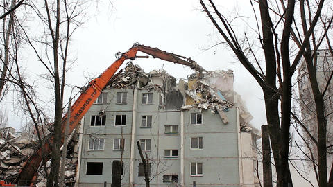 Demolition of building in urban environments with heavy machinery Footage