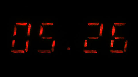 Rapid adjustment of time on the digital clock display, red digits on a black Footage