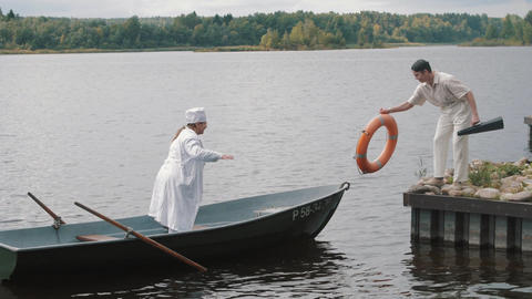 Woman in nurse costume and man in white mooring boat at pier on sunny day Footage